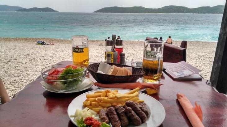Cevapi a la parrila con ensalada todo bien mojado en cerveza croata